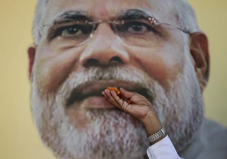 A supporter of Bharatiya Janata Party (BJP) poses with the sweets in front of the portrait of Prime Minister Narendra Modi, as he celebrates after learning of initial poll results outside the party office in Mumbai October 19, 2014. REUTERS/Danish Siddiqui/Files