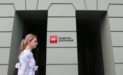 Женщина проходит мимо здания Московской биржи 1 августа 2014 года. Российские фондовые индексы в начале торгов вторника взяли паузу после роста предыдущей сессии. REUTERS/Maxim Shemetov