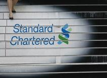 A woman walks down the stairs of the Standard Chartered headquarters in Hong Kong in this October 13, 2010 file photo. REUTERS/Bobby Yip/Files
