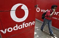 Un hombre habla por su celular mientras pasa entre logos de Vodafone pintados en muros en Kolkata. Imagen de archivo, 20 mayo, 2014.  Vodafone elevó el martes sus previsiones de ganancias tras reportar una fuerte mejoría de su principal medición de ingresos trimestrales debido a una mayor demanda de servicios de telecomunicaciones móviles en sus principales mercados europeos. REUTERS/Rupak De Chowdhuri