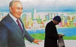 Мужчина проходит мимо постера с изображением президента Казахстана Нурсултана Назарбаева в Алма-Ате 28 ноября 2012 года. Президент Казахстана во вторник приказал правительству ежегодно, с 2015 по 2017 годы, тратить до $3 миллиардов из кубышки, чтобы поддержать рост экономики, пострадавшей от падения цен на нефть и экономического замедления в России. REUTERS/Shamil Zhumatov