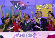 Virgin America Inc. President and Chief Executive Officer David Cush (C) celebrates the company's  initial public offering after ringing the opening bell of the trading session with NASDAQ President and Chief Executive Officer Robert Greifeld (2nd R) at the NASDAQ Market Site in New York, November 14, 2014.  REUTERS/Mike Segar