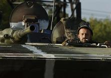 Украинский военный в бронемашине под Горловкой 1 октября 2014 года. Сражающиеся на Украине стороны воззвали к деэскалации конфликта и поддержанию перемирия, отступления от которого волнуют Запад, готовящийся продолжить переговоры с российским лидером Владимиром Путиным на саммите в Австралии. REUTERS/David Mdzinarishvili