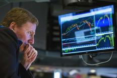 Трейдер на фондовой бирже в Нью-Йорке 31 октября 2014 года. Индекс S&P 500 завершил торги понедельника на рекордном максимуме, так как активность на рынке слияний и поглощений компенсировала опасения по поводу роста зарубежных экономик, вызванные данными о ВВП Японии. REUTERS/Lucas Jackson