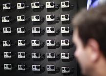Мужчина у стенда GoPro на Consumer Electronics Show (CES) в Лас-Вегасе 8 января 2013 года. Удачно разместившийся в июне производитель камер для экстремальной съемки GoPro объявил цену дополнительного размещения 10.360.500 акций - $75 за штуку. REUTERS/Rick Wilking
