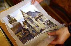 An employee puts away a watercolour of the old registry office in Munich by former German dictator Adolf Hitler at Weidler auction house in Nuremberg November 18, 2014.   REUTERS/Kai Pfaffenbach
