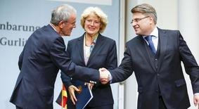 Christoph Schaeublin (L) of the Bern Art Museum and Bavaria's justice minister Winfried Bausback (R) shake hands beside Federal Government Commissioner for Culture Monika Gruetters after signing a contract on the collection from the late Cornelius Gurlitt in Berlin November 24, 2014. REUTERS/Hannibal Hanschke