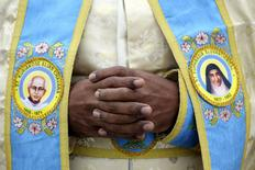 A priest wears vestment depicting two new Indian saints, Kuriakose Elias Chavara (L) and Mother Euphrasia Eluvathingal, as Pope Francis leads a canonization ceremony, to make saints out of six men and women, in Saint Peter's square at the Vatican November 23, 2014.
