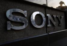 Personas se ven reflejadas en un logo de Sony en Tokio. Imagen de archivo, 16 julio, 2014.  El deficitario grupo japonés Sony tiene previsto recortar las líneas de producción de televisores y teléfonos móviles para reducir costos, pero ve un incremento de miles de millones de dólares en los ingresos por su PlayStation 4 y el negocio de sensores de imagen en los próximos tres años.  REUTERS/Yuya Shino