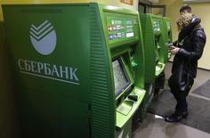 Люди пользуются банкоматами Сбербанка в Санкт-Петербурге 5 ноября 2014 года. Крупнейший банк РФ государственный Сбербанк снизил прогноз рентабельности капитала на 2014 год до около 15 процентов с немного ниже 20 процентов, говорится в презентации банка к отчетности по международным стандартам за третий квартал. REUTERS/Alexander Demianchuk
