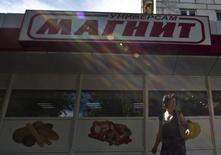 Женщина проходит мимо магазина Магнит в Москве 24 июля 2012 года. Крупнейший в России ритейлер Магнит, уже владеющий крупным производством овощей и зелени на юге, планирует создать 14 новых производств в Краснодаре, под которые местные власти выделили землю, сообщили власти края. REUTERS/Maxim Shemetov