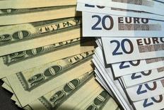 Банкноты доллара США и евро в Париже 28 октября 2014 года. Евро снизился к доллару в четверг, так как инфляция в Германии замедлилась в ноябре, укрепив мнение о том, что Европейский центробанк будет смягчать политику более активно. REUTERS/Philippe Wojazer