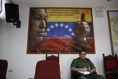 """A student sits in front of an image of Venezuela's late President Hugo Chavez during a lecture of the academic course, """"Studies of the Thoughts of the Supreme Commander Hugo Chavez"""" in Caracas November 19, 2014. REUTERS/Carlos Garcia Rawlins"""