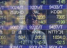 A man is reflected on an electronic stock quotation board outside a brokerage in Tokyo, November 17, 2014. REUTERS/Issei Kato