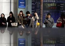 Personas frente una pantalla electrónica que muestra índices económicos en Tokio. Imagen de archivo, 19 noviembre, 2014. El dólar marcó el miércoles un nuevo máximo en siete años contra el yen, lo que ayudó a impulsar al Nikkei a un máximo de cierre similar, y los precios del petróleo rebotaban por la noticia de una caída de los inventarios en Estados Unidos. REUTERS/Yuya Shino
