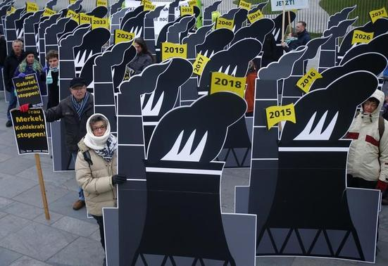 Activists with cardboards symbolizing coal fired power stations protest in front of the chancellery in Berlin December 3, 2014. REUTERS-Michael Hanschke