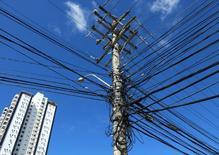 Un poste de tendido eléctrico cubierto de cables en Salvador, Brasil, jul 1 2014. Muchas compañías de Brasil están recortando drásticamente la fabricación de sus principales productos y optan por venderle electricidad a la red nacional por ser un negocio más rentable, lo que refleja las distorsiones que acosan a la economía del país.       REUTERS/Yves Herman