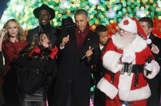U.S. President Barack Obama (C) dances with participants during the 92nd annual National Christmas Tree Lighting on the Ellipse near the White House in Washington December 4, 2014. REUTERS/Yuri Gripas
