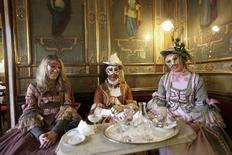 Masked revellers pose inside Caffe' Florian coffee shop in Saint Mark's Square during the Venetian Carnival in Venice in this February 27, 2011 file photo. REUTERS/Manuel Silvestri/Files