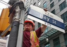 A worker affixes a road sign to the intersection of Bay Street and Adelaide Street in the financial sector of Toronto July 14, 2014.  REUTERS/Chris Helgren