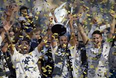Los Angeles Galaxy players from left Juninho , Landon Donovan and Robbie Keane celebrate with the MLS Cup championship trophy after the 2014 MLS Cup final against the New England Revolution at Stubhub Center. Mandatory Credit: Kelvin Kuo-USA TODAY Sports