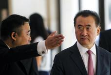 A man shows the way for Wang Jianlin (R), chairman of Wanda, during a meeting with Tencent Chief Executive Officer Pony Ma and Baidu Inc. Chairman and CEO Robin Li, in Shenzhen, Guangdong province, in this August 29, 2014 file photo. REUTERS/Alex Lee/Files