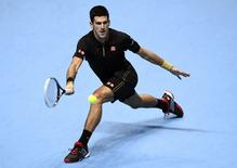 Novak Djokovic of Serbia plays a shot during an exhibition match against Andy Murray of Britain at the ATP World Tour Finals at the O2 in London, November 16, 2014.   REUTERS/Dylan Martinez