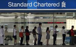 People queue up outside a Standard Chartered Bank branch before operation hours at the central business district in Singapore January 23, 2014. REUTERS/Edgar Su