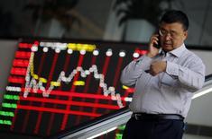 Мужчина говорит по телефону у здания биржи в Шанхае 17 ноября 2014 года. Азиатские фондовые рынки снизились в четверг под влиянием валютного и сырьевого рынков и местных новостей. REUTERS/Carlos Barria