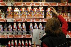 A worker arranges Santa Claus chocolate figurines on a shelf as shoppers take care of their last-minute Christmas gift needs in a mall in Bucharest December 23, 2013. REUTERS/Bogdan Cristel