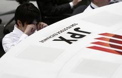 Сотрудник Токийской фондовой биржи на работе 16 октября 2014 года. Азиатские фондовые рынки, кроме Китая, снизились в понедельник на фоне падения цен на нефть до минимума 5,5 лет. REUTERS/Yuya Shino