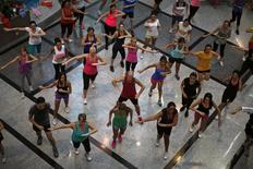People take part in an aerobics class at a shopping centre in Malaga, southern Spain, August 1, 2014. Picture taken August 1, 2014. REUTERS/Jon Nazca