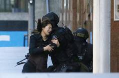 Une des otages ayant réussi à sortir du café Lindt, dans le centre de Sydney, où un homme armé retient un nombre indéterminé de captifs. Un drapeau noir avec des inscriptions blanches en arabe à la fenêtre fait craindre une attaque de sympathisants islamistes. /Photo prise le 15 décembre 2014/REUTERS/Jason Reed
