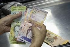 Una cajera cuenta bolívares en un supermercado en Caracas, sep 9 2014. Los bonos de la deuda venezolana ampliaban sus pérdidas el martes, en línea con el retroceso de los precios internacionales del petróleo que rompían nuevas barreras psicológicas obligando a los inversores a buscar refugio en activos menos riesgosos. REUTERS/Carlos Garcia Rawlins