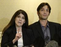 Michael Egan (R), who sued filmmaker Bryan Singer for allegedly raping him as a teenager, sits next to his mother Bonnie Mound as she speaks during a news conference at a hotel in Los Angeles April 21, 2014.  REUTERS/Kevork Djansezian