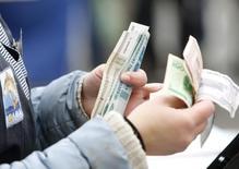 Уличный торговец пересчитывает белорусские рубли в Минске 5 октября 2013 года. Белорусский президент Александр Лукашенко сказал, что Белоруссия не будет девальвировать национальную валюту, несмотря на падение курса российского рубля и потребовал перейти на расчеты с Россией в долларах и евро, передало государственное агентство БелТА. REUTERS/Vasily Fedosenko