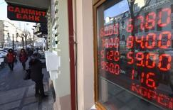 """A board showing currency exchange rates is on display in the Russian far eastern city of Vladivostok, December 18, 2014. Russia's rouble lost more ground against the dollar on Thursday before President Vladimir Putin's end-of-year news conference, expected to be dominated by what a government minister called a """"perfect storm"""" hitting the economy. REUTERS/Yuri Maltsev (RUSSIA - Tags: BUSINESS POLITICS)"""