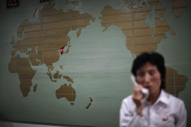 A world map, with the Korea peninsula marked in red, is seen as a hotel receptionist talks on the phone in Rason city, northeast of Pyongyang, August 29, 2011. REUTERS/Carlos Barria