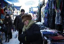 Китаянка продает вещи на рынке в Иркутске 13 февраля 2010 года. Дом китаянки Моу Цзянь в российском Благовещенске, расположенном на границе с Китаем, превратился в склад - помещение захламлено новыми iPhone, женскими сумочками и молочным порошком - все из этого появилось здесь благодаря резкому падению курса российской валюты и скоро отправится в Поднебесную. REUTERS/Denis Sinyakov