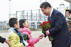 Chinese President Xi Jinping shakes hands with a child as he receives a bouquet upon arriving in Macau to celebrate the 15th anniversary of its handover to the mainland December 19, 2014. REUTERS/Government Information Bureau of the MSAR/Handout via Reuters