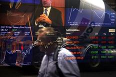 A pedestrian is reflected in the window of the Australian Securities Exchange with boards displaying stock movements in central Sydney September 24, 2014. REUTERS/David Gray