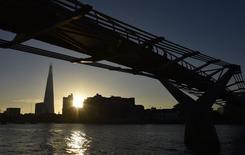 Trabajadores cruzan el puente Millenium en la ciudad de Londres. Imagen de archivo, 16 diciembre, 2014. El gasto de los hogares impulsó la recuperación económica de Gran Bretaña nuevamente en el tercer trimestre, pese a una leve caída de los ingresos disponibles y de un crecimiento más débil de las inversiones empresariales que lo informado previamente, mostraron datos oficiales publicados el martes. REUTERS/Toby Melville