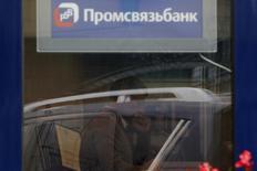 Сотрудник в отделении Промсвязьбанка в Москве 4 октября 2012 года. Рост кредитного портфеля Промсвязьбанка подъел капитал банка, заработки которого уменьшились из-за роста резервов и убытков по финансовым инструментам, но были подкреплены переоценкой опциона на покупку ассоциированной компании-застройщика. REUTERS/Maxim Shemetov