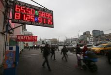 Unas personas pasan junto a una casa de cambios en Moscú, dic 17 2014. Standard & Poor's colocó el martes el panorama de la calificación soberana de Rusia en revisión con perspectiva negativa, desde negativo, en medio de una revisión de la flexibilidad monetaria y una debilitada economía. REUTERS/Maxim Zmeyev