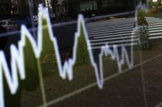 Una mujer empujando un carro se ve reflejada en una pantalla electrónica que muestra las fluctuaciones del índice Nikkei en Tokio, 24 diciembre, 2014.  El índice Nikkei de la bolsa de Tokio saltó el miércoles después de que Wall Street tocó un máximo histórico de cierre en la sesión anterior por unos datos que revelaron un crecimiento sólido de la economía estadounidense. REUTERS/Yuya Shino