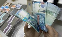 Сотрудник отделения Казкоммерцбанка считает тенге в Алма-Ате 4 февраля 2010 года. Правительство Казахстана обещает не допустить резких колебаний курса тенге в 2015 году после проведенной в феврале 19-процентой девальвации национальной валюты и на фоне падения курса рубля в соседней России, говорится в заявлении кабмина, опубликованном на официальном сайте в среду. REUTERS/Shamil Zhumatov