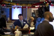 Unos operadores trabajando en la bolsa de Wall Street en Nueva York, dic 23 2014. Las acciones están mostrando el tipo de volatilidad que en el pasado precedió a grandes caídas, por lo que algunos creen que una de las más escaladas más agresivas que se ha visto en Wall Street podría estar llegando a su fin.     REUTERS/Carlo Allegri