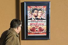 """A man walks by the poster for the film """"The Interview"""" outside the Alamo Drafthouse theater in Littleton, Colorado December 23, 2014.   REUTERS/Rick Wilking"""