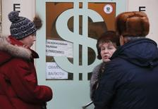 Люди у пункта обмена валюты в Москве 17 декабря 2014 года. Российская валюта достигла трехнедельных максимумов, отправив валюту США под отметку 52 рубля за счет небольших объемов экспортных продаж в условиях чрезвычайно тонких в западное Рождество рынков. REUTERS/Maxim Zmeyev
