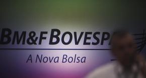 Un hombre habla por su teléfono frente al logo del BM&FBovespa en la bolsa de Brasil. Imagen de archivo, 7 octubre, 2013. El principal índice de acciones de Brasil caía el viernes, tras el feriado de la víspera, en un día que se espera de baja liquidez y con la petrolera Petrobras nuevamente como el centro de la atención del mercado. REUTERS/Nacho Doce